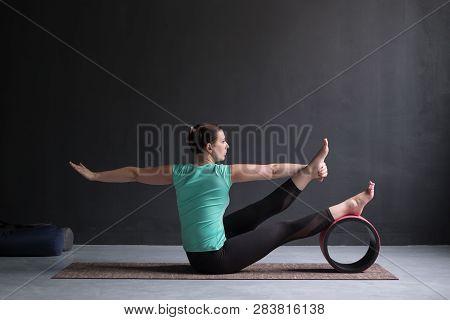Yoga girl doing parivrtta navasana or twisted boat pose stock photo