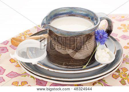 Kefir in argil jug with wooden spoon on rustic plate. stock photo