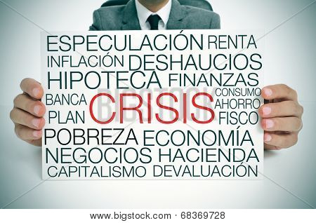 a businessman holding a signboard with different terms in spanish related to the economic crisis concept stock photo