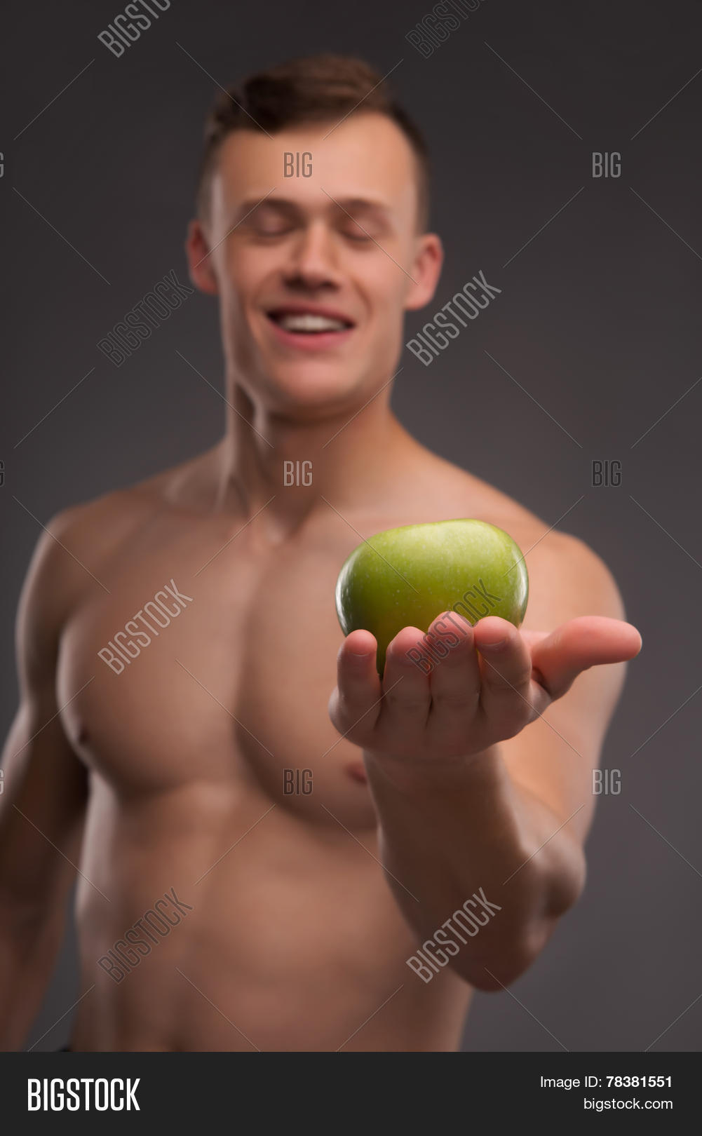 Selective focus on the delicious green apple lying on the palm of the young handsome smiling fair-haired bare-chested karate enthusiast standing on background