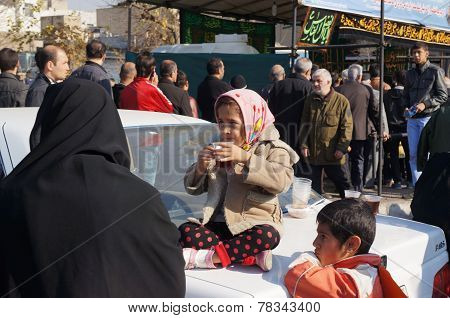 TEHRAN, IRAN - 13 DECEMBER 2014: Little girl drinks tea on a car on a religious holiday Arbaeen ** Note: Soft Focus at 100%, best at smaller sizes stock photo