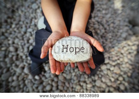Child on a beach with hands cupped holding stone pebble with the word hope engraved concept for fait