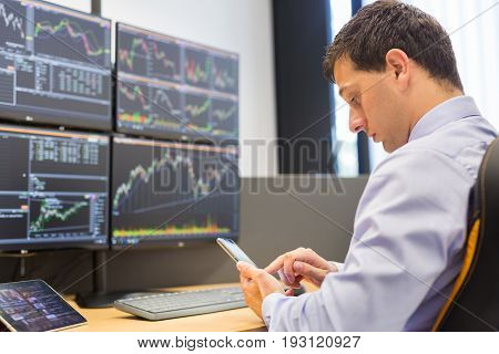 Stock broker trading online while accepting orders by phone. Trader's office with multiple computer screens full of index charts and data analyses. stock photo