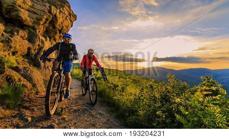 Mountain biking women and man riding on bikes at sunset mountains forest landscape. Couple cycling M