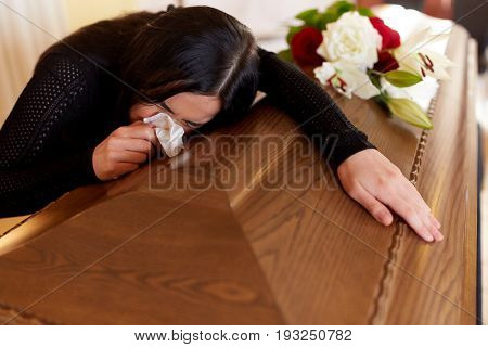 people and mourning concept - crying woman with coffin at funeral in church stock photo
