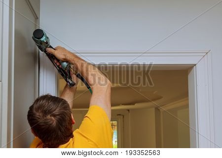 Carpenter brad using nail gun to moldings on doors framing trim with the warning label that all power tools have on them shown illustrating safety concept stock photo