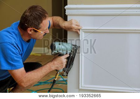 Unrecognizable handyman nailed up Picture Moulding wall in the new house stock photo