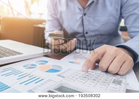 Business Financing Accounting Banking Concept businessman using smart phone and doing finances calculate about cost to real estate investment and in other tax system.