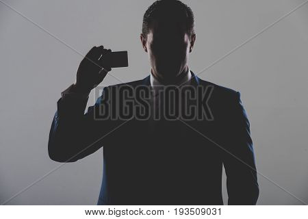 silhouette of man businessman or manager holding business or bank card in blue formal suit on grey background. Shadow business and economy banking fraud skimming ecash and information