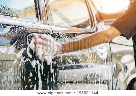 Auto service staff cleaning a car with sponge and car wash-car detailing and valeting concepts. stock photo
