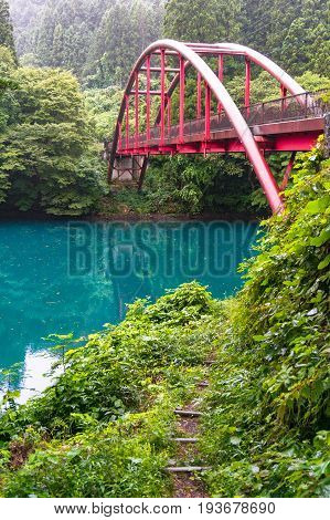 Picturesque view of red bridge over turquoise water river in forest on rainy day. Shima lake Japan stock photo