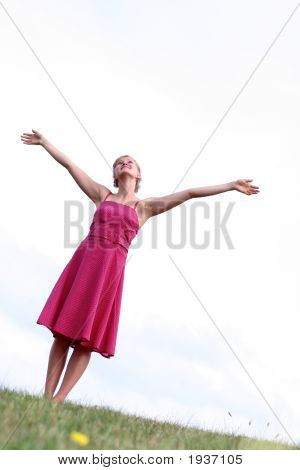 Woman Standing on Grass with Arms Outstretched stock photo