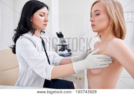 Beautiful young woman getting her breast examined by female doctor gynecologist profession experience trust feminine health medical clinical survey cancer prevention consciousness. stock photo
