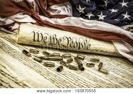 The United States Constitution rolled up on an American flag with bullets scattered about symbolizing the second amendment. stock photo