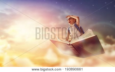 Back to school! Happy cute industrious child flying on the book on background of sunset sky. Concept