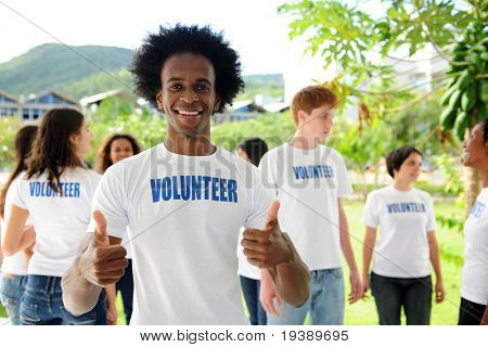 happy volunteer african american man showing thumbs up sign and group stock photo