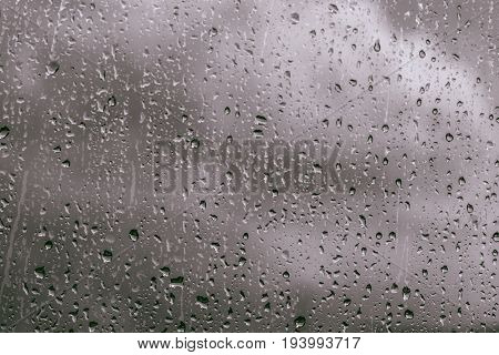 Rain drops on window glasses background. Natural Pattern of raindrops isolated on cloud background. stock photo