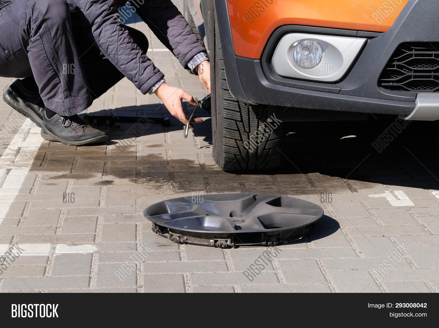 Man Is Changing Wheel After A Car Break Down. Damaged Car Tyre. Wheel Balancing Or Repair And Change