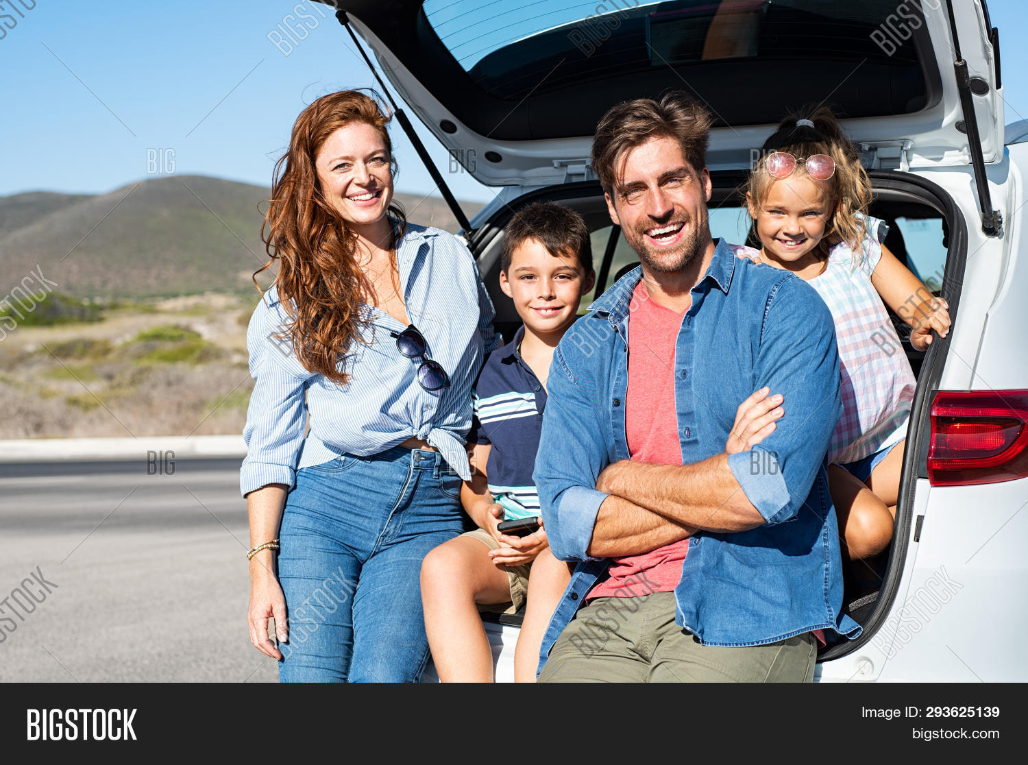 Smiling family with two kids sitting in car trunk and looking at camera. Happy children enjoying wit