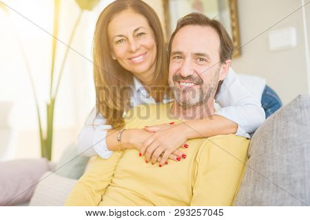 Middle age romantic couple sitting on the sofa at home stock photo
