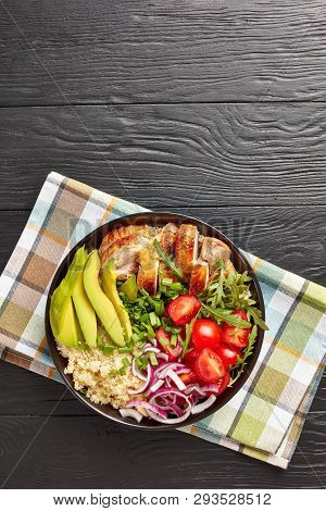 healthy chicken bowl with couscous, fresh vegies, avocado and arugula on a wooden black table, vertical view from above stock photo