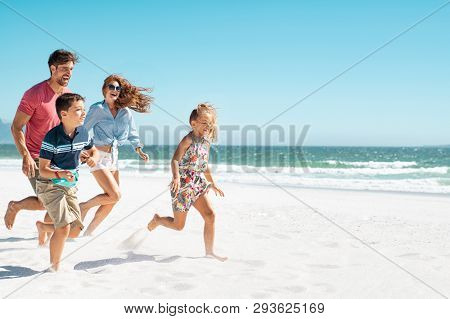 Cheerful young family running on the beach with copy space. Happy mother and smiling father with two