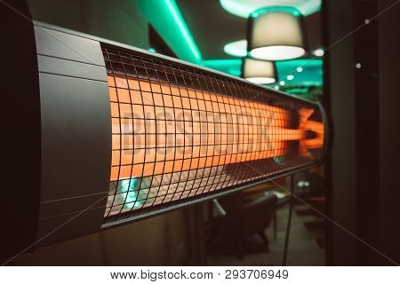 The electric heater in the room. heating the apartment in cold weather. Halogen or Infrared heater isolated on a white background stock photo