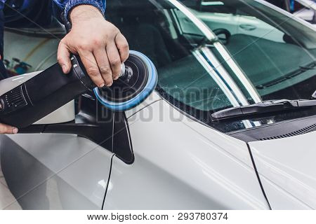 Car detailing - Hands with orbital polisher in auto repair shop. Selective focus. stock photo