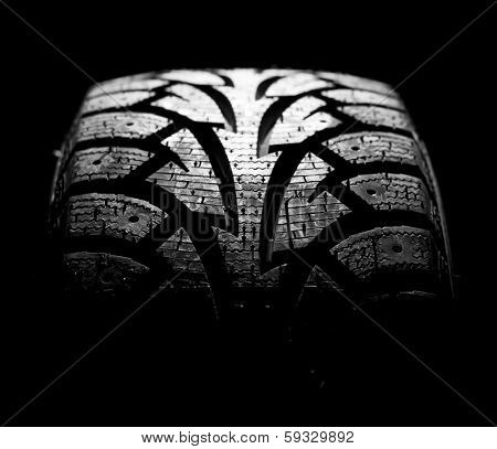 winter car tyre on a black background stock photo