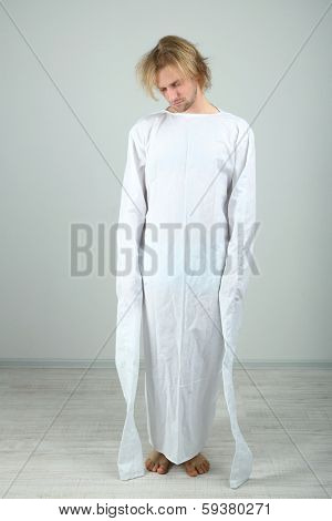 Mentally ill man in strait-jacket on gray background stock photo
