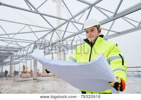 male engineer construction foreman manager outdoors indoors at building site with blueprints stock photo