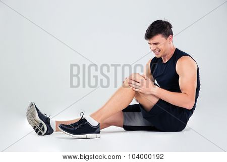 Portrait of a fitness man suffering from pain in a knee isolated on a white background stock photo