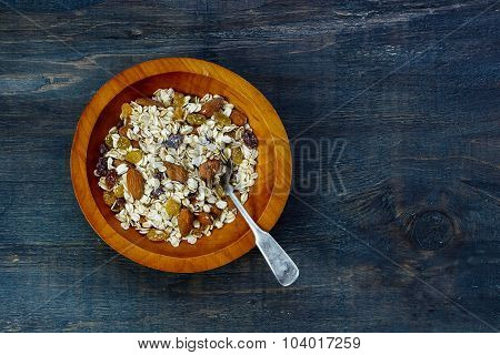 Healthy breakfast - muesli in wooden bowl over dark background with space for text. Health and diet concept. stock photo
