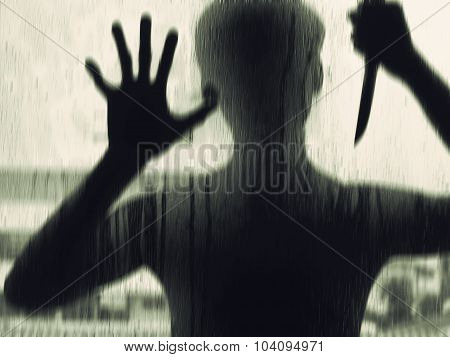 Shadowy figure with a knife behind glasssoft focus,soft Focus stock photo