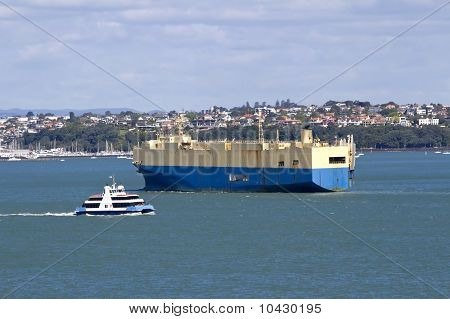 A container carrier leaves port dwarfing the harbour ferry heading to its berth stock photo