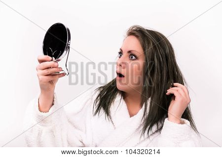 brown haired woman looking shocked at herself in a mirror while wearing a bathrobe stock photo