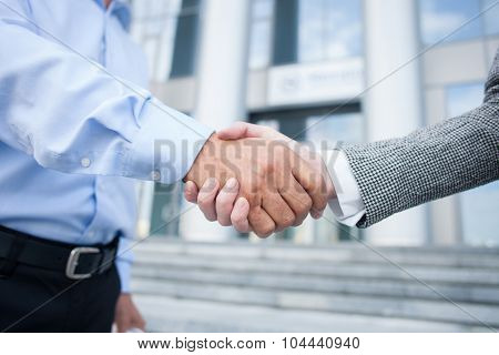 Close up of arms of colleagues shaking hands. The man and woman are standing near building outside stock photo