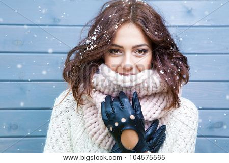 Winter portrait of young beautiful brunette woman wearing knitted snood covered in snow. Snowing win