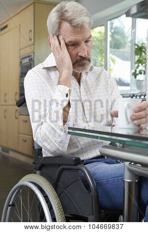 Depressed Woman Sitting In Wheelchair At Home stock photo
