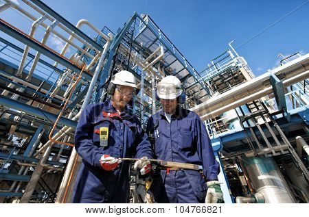 two oil and gas workers with main station at refinery industry