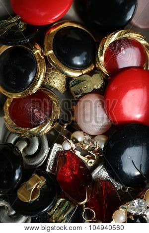 Variety dozens different colour golden silver old-fashioned time-worn used vintage bijouterie collection of imitation jewellery frosted transparent glazy dum earclips piled together vertical picture stock photo