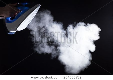 Modern iron blowing off steam on black background stock photo