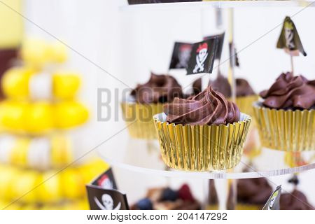 Close-up of cupcakes on stand in yellow and black colors pirate theme for kids birthday party stock photo