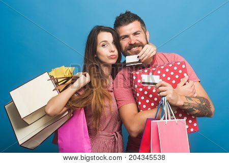 Guy with beard and lady do shopping. Shopping and fashion concept. Bearded man with smiling face holds pink packets. Couple in love hugs holding shopping bags and credit cards on blue background. stock photo