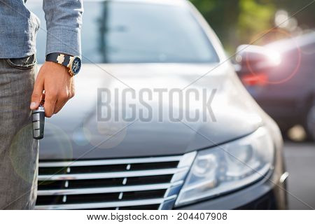 Buying used car. Car Dealer Inventory. Used cars store. Male wants to buy the car. Close-up of hand with a wrist watch, holding key from auto, finance for car concept. Happy life. Blurred background. stock photo