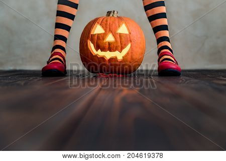 Funny child dressed witch costume. Kid painted terrible pumpkin. Halloween autumn holiday concept stock photo