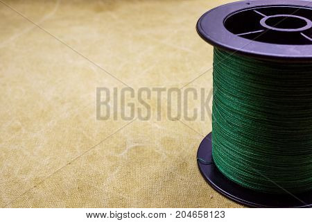 Spool of cord on the background of tarpaulin. Green fishing line on tarpaulin. Spool of braided fishing line stock photo