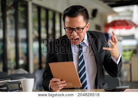 Asian angry businessman wearing glasses white shirt black suit looking and yelling at digital tablet after getting bad news from digital tablet. Raising hand and screaming at monitor on work table. stock photo