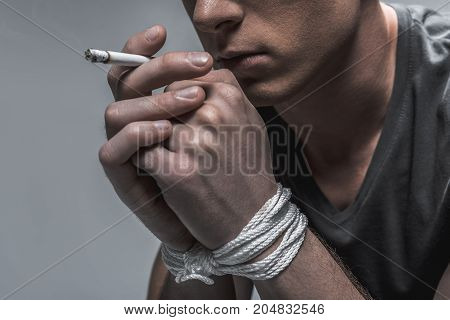 Realizing problems with self-control. Close up of pensive young man smoking cigarette. His hands are tied up with a rope. Isolated and copy space in left side stock photo