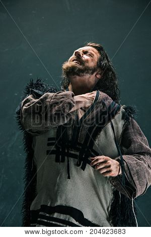 Actor in makeup, a poor man on black studio background. The bum in canvas rags. concept of vagrancy and survival stock photo